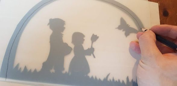 Festes Transparentpapier wird als Hintergrund für das Fensterbild ausgeschnitten.